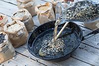 Selbstgemachte Fettfuttermischung, Kokosfett wurde in der Pfanne erhitzt, nun wird eine Körnermischung hinzugeschüttet, Fettfutter aus Kokosfett, Sonnenblumenkernen, Erdnussbruch, Körnermix, Körnermischung, Sonnenblumenöl, Vogelfutter selbst herstellen, Vogelfutter selber machen, Vogelfutter selbermachen, Vogelfütterung, Fütterung, bird's feeding