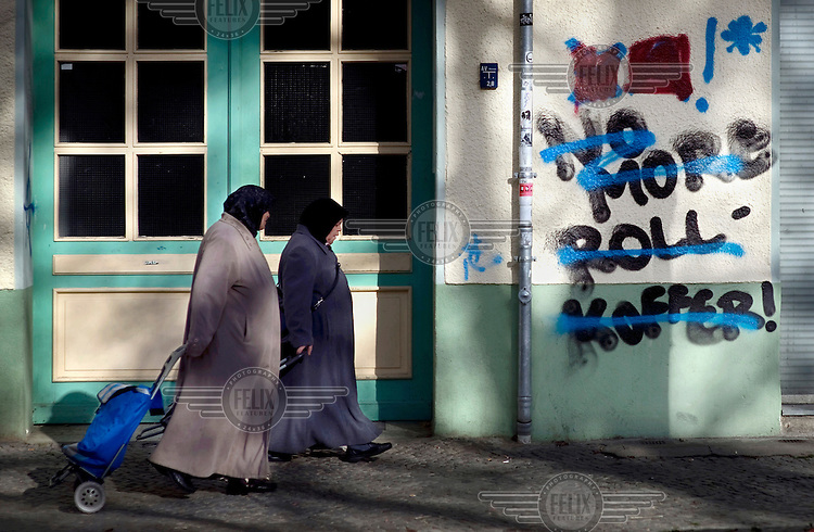 Women walk past graffiti reading No More Rollkoffer, no more suitcases, at the Schillerkiez in Berlin Neukoelln. The suitcases refers to the high number of tourists now descending on this part of the city. This graffiti is just one sympton of a steady process of gentrification which is rapidly forcing poorer residents out of the city centre and tearing apart the city's social fabric.