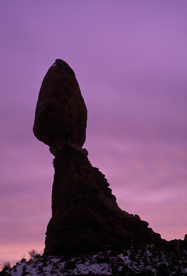 Balanced Rock silhouetted against sunrise lit clouds, Arches National Park, Utah.
