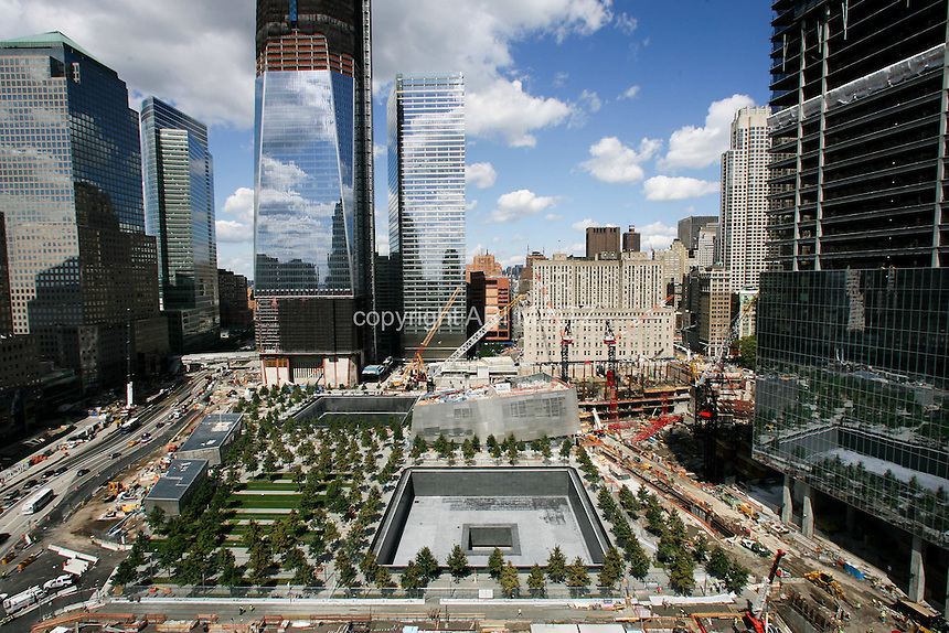 Tenth anniversary of 9/11.  Rebuilding at the World Trade Center site.  The view from south side of site shows L to R: World Financial Center, Goldman Sachs, 1 WTC, 7 WTC, the postal building and the under-construction 4 WTC.   The 9/11 Memorial is situated around the footprints of the original towers.   Photo by Ari Mintz.  8/22/2011.