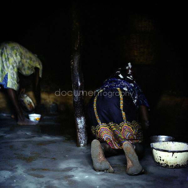 women from the camp fixing the floor of their hut.