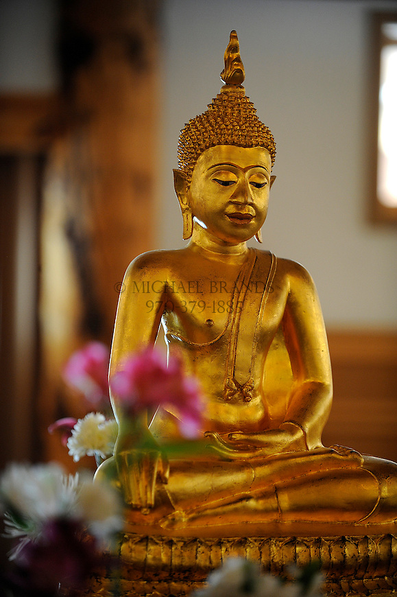 Surrounded by flowers and offerings, a Buddha figure graces the altar inside the Zendo at the Crestone Mountain Zen Center. Michael Brands for The New York Times.