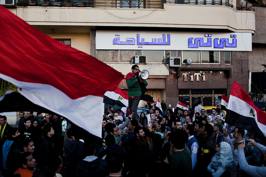 A crowd of protesters passes an apartment building during a protest from Tahrir Square toward the 'Maspero' Ministry of Information building, Cairo, January 25, 2012. Protsters marked the first anniversary of the Egyptian revolution by packing into the city's infamous Tahrir Square. An overflow of protesters moved on to the Maspero building that afternoon. Photo: Ed Giles.