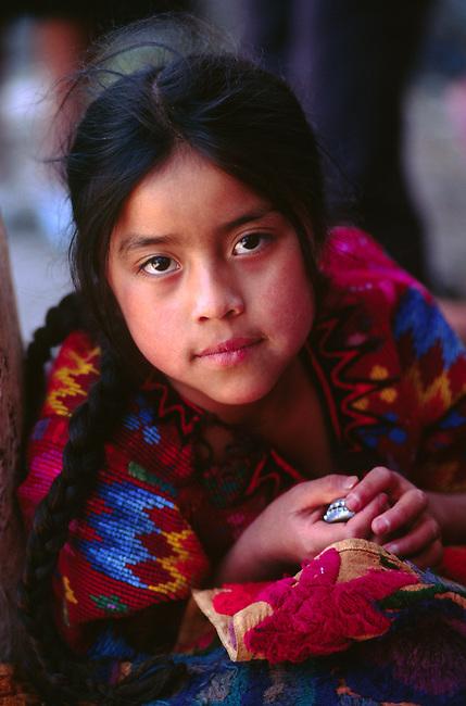 GUATAMALAN GIRL wearing traditional brocade HUIPIL in MARKETPLACE - CHICHICASTENANGO, GAUTAMALA