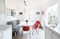 The modernised kitchen is furnished with a Zinotta surf table and a collection of red stacking chairs and the banquette is covered in an Ikat design from Christopher Farr's Cloth range.