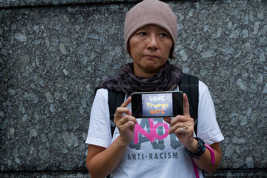 "A Japanese  woman holds a smart phone with the message ""Love Trumps Hate""  at the  ""Enough is Enough"" rally in Toranomon, Tokyo Japan, Tuesday August 15th 2017. Around 20 people gathered to take part in a global day of action demanding fairer policies in the United States that do not favour only the rich and do not remove human rights from ordinary people. A silent vigil was held for 30 minutes at 6pm so that the voices that could be heard after spoke louder. This is the closest it is possible to protest to the US embassy in Tokyo."