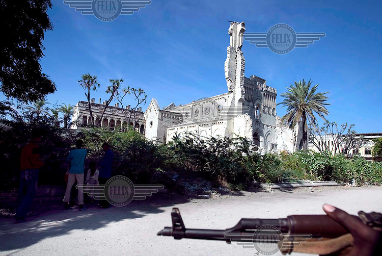 A gunman with an AK47 in front of the ruins of the once picturesque Mogadishu Cathedral, which is located on the Green Line which divides the city. The cathedral was built by Somalia's Italian colonists in 1929, but was largely destroyed in fighting between rival clans in 1993.