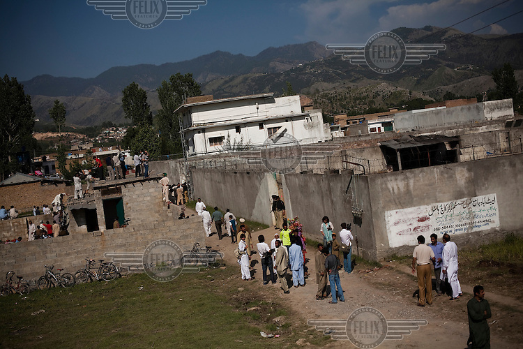 Local residents and media gather outside the compound, less than a kilometre from the Pakistan's biggest military academy, where Osama Bin Laden was killed in an operation by US Navy Seals on 3 May 2011. Following the attack, code-named Operation Neptune Spear, American forces took bin Laden's body to Afghanistan for identification and then buried it in the Arabian Sea.