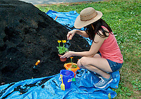 Woman potting marigolds at an earth day event.