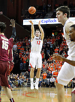 Virginia guard Joe Harris (12) shoots a three point basket between Florida State  defenders during the second half of an NCAA basketball game Saturday Jan. 18, 2014 in Charlottesville, VA. Virginia defeated Florida State 78-66. Virginia defeated Florida State 78-66. (AP Photo/Andrew Shurtleff)