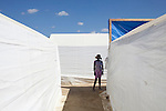 A woman stands between tents at a cholera clinic on Friday, November 26, 2010 in Cabaret, Haiti.
