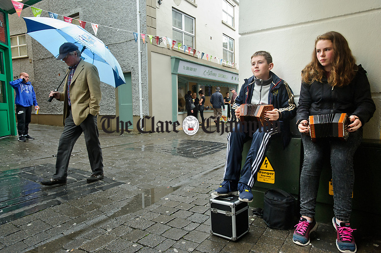 Liam and Lea Labat performing on Parnell street during a wet final Sunday of the All-Ireland Fleadh in Ennis. Photograph by John Kelly.