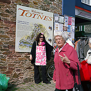 Transition Town Series. March 2011. Totnes, Devon. Poet Jackie Juno, the Bard of Exeter, under the 'Welcome to Totnes' sign. She writes environmentally minded subverted nursery rhyme poetry. Here are some of her poems:..Jack and Jill went up the hill.cos everywhere else was flooded. ..London Bridge is falling down falling down falling down.London Bridge is falling down.due to the sea level rising...Pussycat Pussycat where have you been?.I've been to Burma but I can't talk about it.