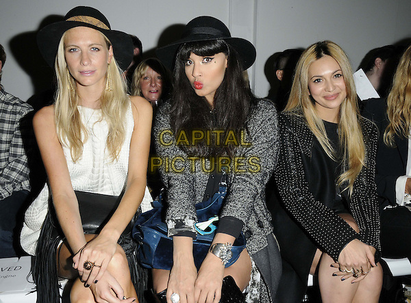 Poppy Delevigne, Jameela Jamil & Zara Martin.at the Zoe Jordan s/s 2013 catwalk show, London Fashion Week  LFW Day 1, Mercer Street Studios, Mercer Street,  London, England, UK, .14th September 2012..half length sitting front row black studded leather sleeve leather dress hat grey gray coat white .CAP/CAN.©Can Nguyen/Capital Pictures.