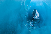Incredible blue glacial colours, shapes and texture of ice tunnel made by running melt water on Franz Josef Glacier, Westland Tai Poutini National Park, West Coast, UNESCO World Heritage Area, New Zealand, NZ