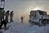 """Workers signal a snow tank to reverse in the colony set up by oil and gas prospecting company """"Siesmorevzedka"""" in the Arctic tundra. Typically, they work in the cold, isolated Arctic tundra for the entire winter, returning to civilisation only in spring."""