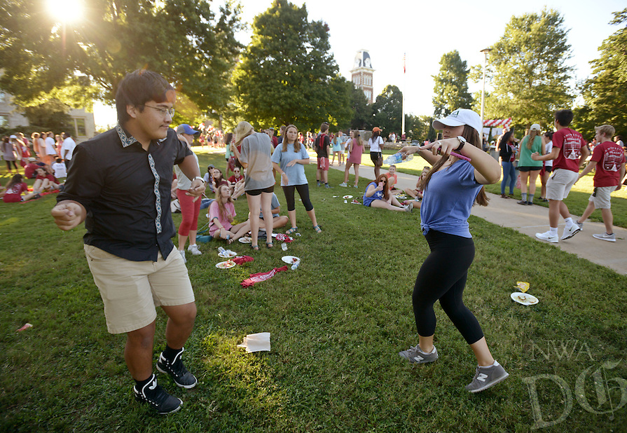 NWA Democrat-Gazette/BEN GOFF @NWABENGOFF<br /> Katie Hilburn, a freshman student from Carrollton, Texas, and Eizhar Anware, a freshman from China, dance on Sunday Aug. 21, 2016 during the New Student Welcome and Burger Bash on the University of Arkansas campus in Fayetteville.