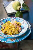 A bowl of mafaldine pasta with saffron and prawns