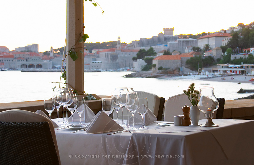 A dining table set with glasses and starched napkins, view of the old town in the background from the luxury Excelsior Hotel and Spa restaurant terrace Dubrovnik, old city. Dalmatian Coast, Croatia, Europe.