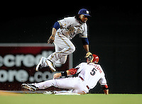 May 7, 2010; Phoenix, AZ, USA; Arizona Diamondbacks base runner Cole Gillespie slides into the game ending double play as Milwaukee Brewers second baseman Rickie Weeks leaps over following his throw to first to end the game at Chase Field. The Brewers defeated the Diamondbacks 3-2. Mandatory Credit: Mark J. Rebilas-