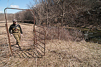 An angler walks through a gate in a cattle fence along the Green River a trout stream in the Driftless Area of southwestern Wisconsin.