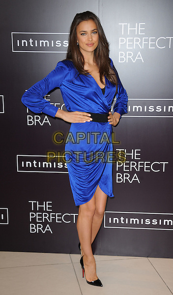 Irina Shayk (Irina Shaykhlislamova).launches Intimissimi Perfect Bra Collection and book at.Intimissimi, Oxford Street, London, England 24th April 2012.full length blue wrap dress black belt hands on hips.CAP/WIZ.© Wizard/Capital Pictures.