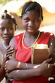Kalepo, Tanzania. Two Africa girls, one holding a missal in local language and wearing a red dress and yellow beads.