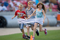 Three children race in a giant pair of underpants between innings at Five County Stadium August 15, 2009 in Zebulon, North Carolina. (Photo by Brian Westerholt / Four Seam Images)