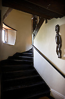 An African sculpture is displayed on the whitewashed walls of the twisting oak staircase