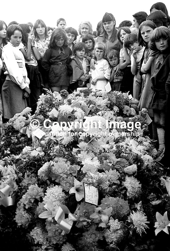 Mourners view the floral tributes at the grave of the three Maguire children, Joanne, 8 years, John, 2 years, and Andrew, 6 weeks, who died as a result of one of the most tragic and horrific incidents of the N Ireland Troubles on 10th August 1976. A car driven by Daniel Lennon, aka Danny Lennon, member, Provisional IRA,  mounted the pavement and ploughed into the Maguire family. Lennon died at the wheel having been shot by British soldiers in hot pursuit. The incident gave rise to the birth of the Peace People organisation led by Mairead Corrigan, aunt of the dead children, and a local woman,Betty Williams. 197608130371d.<br /> <br /> Copyright Image from Victor Patterson,<br /> 54 Dorchester Park, <br /> Belfast, UK, BT9 <br /> <br /> t1: +44 28 9066 1296 (from Rep of Ireland 048 90661296)<br /> t2: +44 28 9002 2446 (from Rep of Ireland 048 9002 2446)<br /> <br /> m: +44 7802 353836<br /> <br /> e: victorpatterson@me.com<br /> www.victorpatterson.com<br /> <br /> Please see my Terms and Conditions of Use at www.victorpatterson.com. It is IMPORTANT that you familiarise yourself with them.<br /> <br /> Images used on the Internet must be visibly watermarked i.e. &copy; Victor Patterson<br /> within the body of the image and copyright metadata must not be deleted. Images <br /> used on the Internet have a size restriction of 4kbs and will be chargeable at current<br />  NUJ rates unless agreed otherwise.<br /> <br /> This image is only available for the use of the download recipient i.e. television station, newspaper, magazine, book publisher, etc, and must not be passed on to any third <br /> party. It is also downloaded on condition that each and every usage is notified within 7 days to victorpatterson@me.com<br /> <br /> The right of Victor Patterson to be identified as the author is asserted in accordance with The Copyright Designs And Patents Act (1988). All moral rights are asserted.