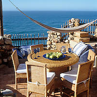 The cane chairs and table on the terrace overlook the ocean and the sun-bathing 'pit'