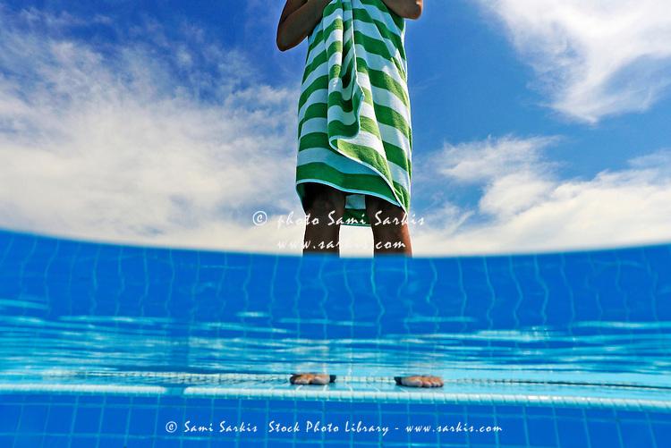 Woman standing on swimming pool ledge (split shot)