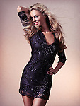 Fashion photo of a beautiful smiling woman with flying long blond hair wearing a black dress
