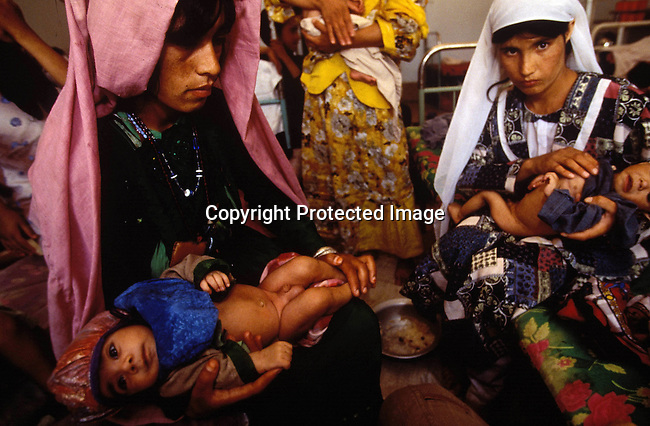 COAFGHA35020.Country. Afghanistan. Herat. Two malnourished children held by two women. 9/96..©Per-Anders Pettersson/iAfrika Photos