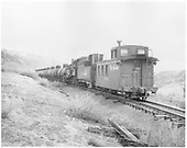K-36 #483 pushing a load of tank cars up to Cumbres with long caboose #04343 trailing; end-side view of caboose, flying herald. Photographer could be Otto Perry, but unknown.<br /> D&amp;RGW