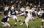 Nevada's Brent Zuzo kicks a point-after past UC Davis defender Patrick Wells during an NCAA college football game in Reno, Nev. on Thursday, Sept. 3, 2015. Nevada holder Alex Boy is at left. (AP Photo/Cathleen Allison)