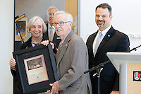 NWA Democrat-Gazette/DAVID GOTTSCHALK  Joyce and Jim Faulkner (from left) stand with Todd Shields, dean of the J. William Fulbright College of Arts and Sciences, Friday, September 18, 2015 after receiving a gift in the lobby of the new Jim and Joyce Faulkner Performing Arts Center on the campus in Fayetteville. Jim and Joyce Faulkner made a $6 million donation to the university in 2012 specifically toward renovating and remodeling the Field House into a performing arts center.