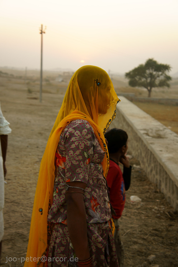 woman and child at camel fair in holy city Pushkar while sunset time