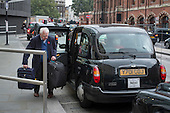 An elderly man with suitcases boards a black cab taxi in Kings Cross London
