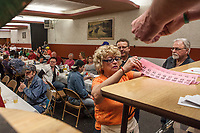 The green wheel of a meat raffle, the organizers table with cash and a list of prizes and  the bowling pins for a frozen turkey bowling sessionn at the Moose Lodge in Lancaster, NY. Meat raffles have become poular fundraisers in Western New York. April 2016. Photo by Brendan Bannon