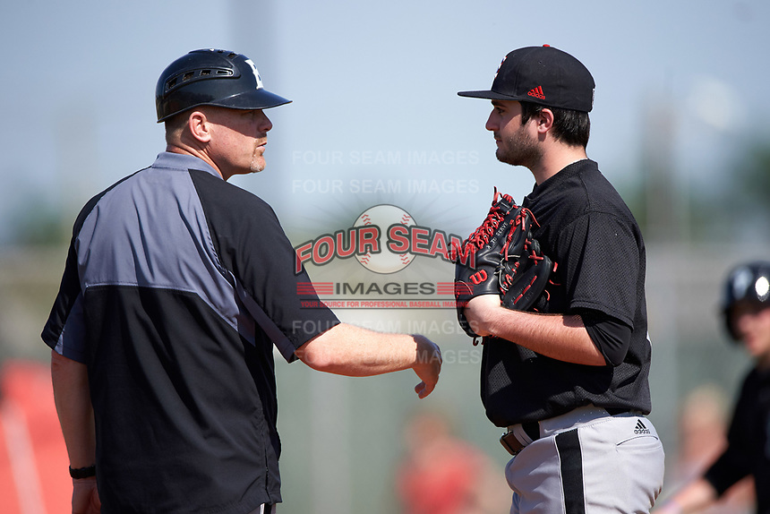 Edgewood Eagles head coach Al Brisack talks with pitcher pitcher Bryce Lashley (31) during the first game of a doubleheader against the Plymouth State Panthers on April 17, 2016 at Lee County Player Development Complex in Fort Myers, Florida.  Plymouth State defeated Edgewood 6-5.  (Mike Janes/Four Seam Images)