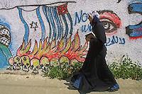 A Palestinian woman passes by graffiti outside the Islamic University in Gaza City. Photo by Quique Kierszenbaum