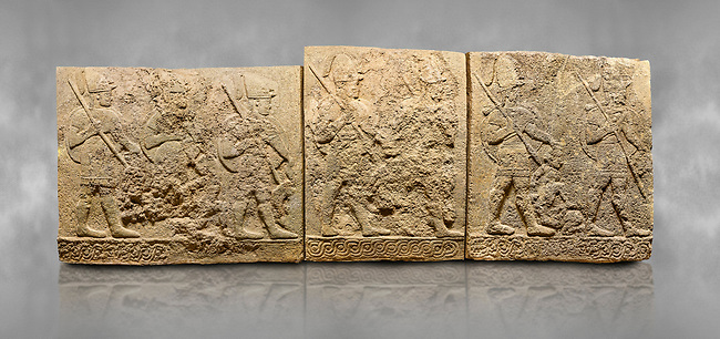 Hittite sculpted orthostats panels of Long Wall Limestone, Karkamıs, (Kargamıs), Carchemish (Karkemish), 900-700 B.C. Soldiers. Anatolian Civilisations Museum, Ankara, Turkey<br /> <br /> Figures of helmeted warriors. They have their shield in their back and their spear in their hand. The prisoner in their front is depicted as small. The lower part of the orthostat is decorated with braiding motifs. <br /> <br /> On a grey art background.