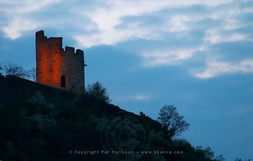The ruin of a tower in the town Tournon in the Rhone Valley. Floodlit at night in silhouette against an evening blue sky. Tournon-sur-Rhone, Ardeche Ardèche, France, Europe