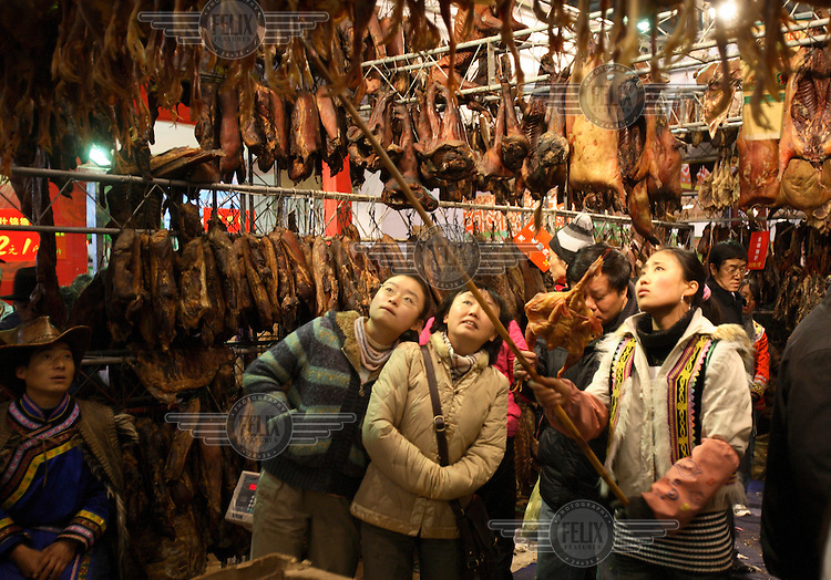 A family of three try to decide on their purchase of cured and salted meats at a Chinese New Year food fair in Chengdu.