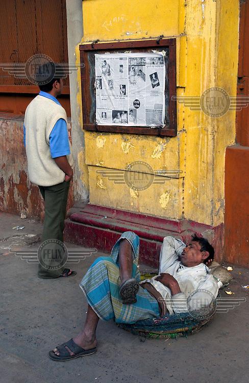 A man reads a newspaper pinned up on the street. Beneath him, a homeless man sleeps.