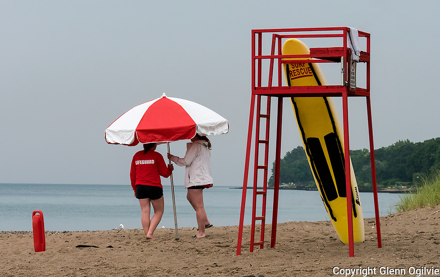 Sometimes life guarding at Canatara Park beach can be a lonely job if there's only two people on the beach to guard. These two lifeguards were seen huddled under an umbrella trying to keep dry during showers.<br /> <br /> Erika Lange, red top, a five year veteran lifeguard at Canatara park beach and Mackenzie Turner, four year lifeguard. Erika is attending Western University teachers college and Mackenzie is studying French at the University of Guelph.