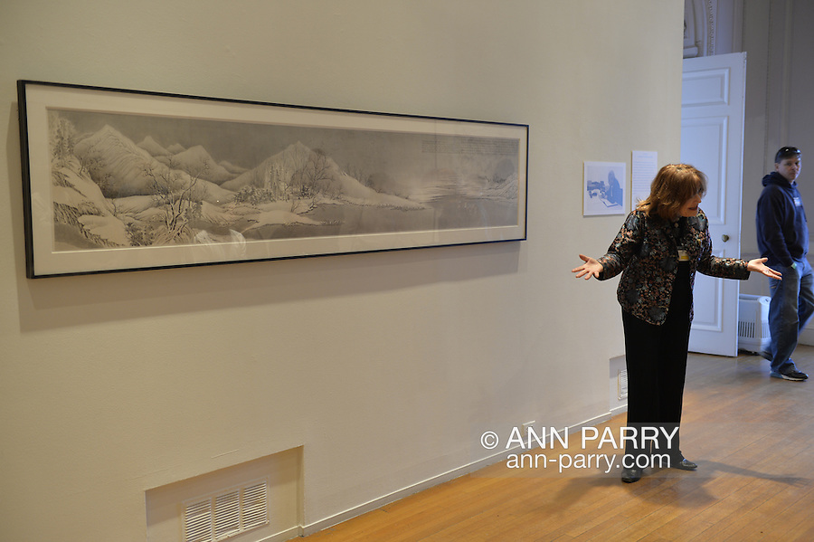 Roslyn, New York, USA. January 2, 2015. LINDA SCHWARTZ, a docent shares information about the artwork exhibits at the Nassau County Museum of Art China Now and Then Exhibit on Long ISland. Art on wall by is Chinese artist Liu Dan (b. 1953) Winter Landscape, 2002, Ink on paper, 24 3/4 x 102 1/2 inches.