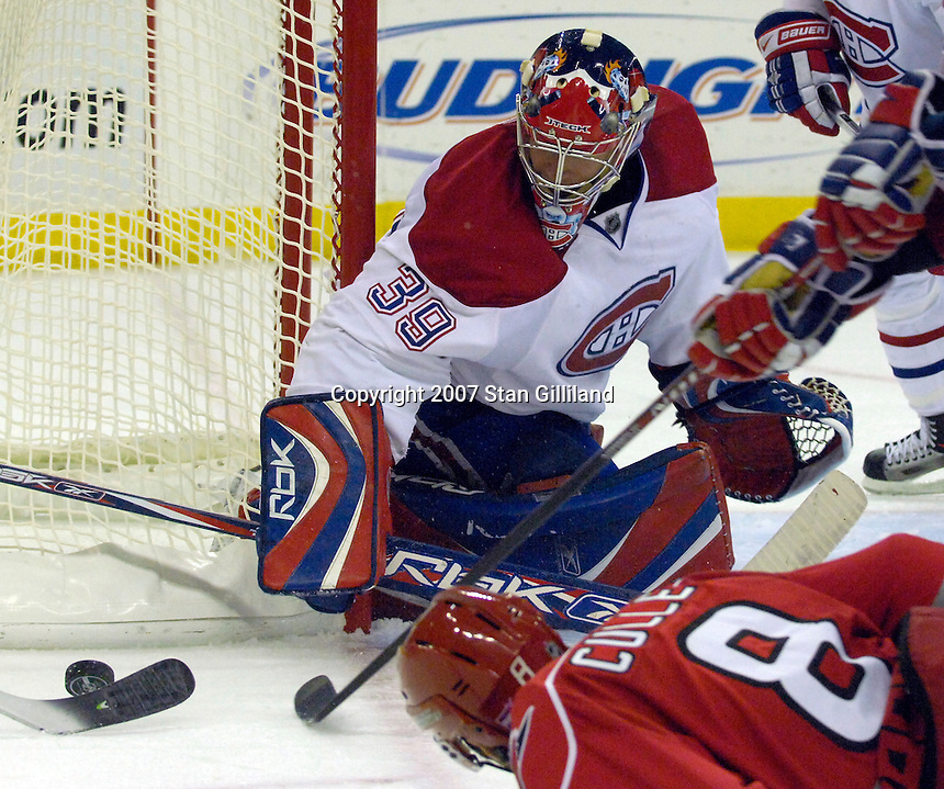 Montreal Canadiens' goalie Cristobal Huet and the Carolina Hurricanes' Matt Cullen (8) reach for a puck during their game Friday, Oct. 26, 2007 in Raleigh, NC. The Canadiens won 7-4.