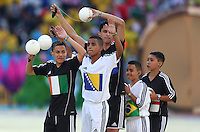 Children wave footballs in the air as part of the opening ceremony of the 2014 FIFA World Cup